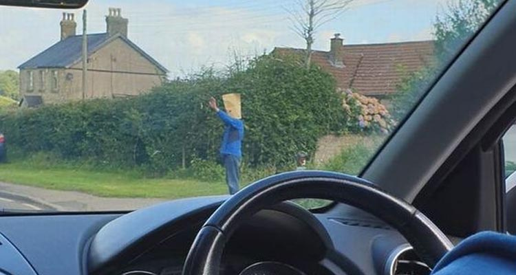 Mystery surrounds man who stands at the side of a road waving at cars with a bag on his head