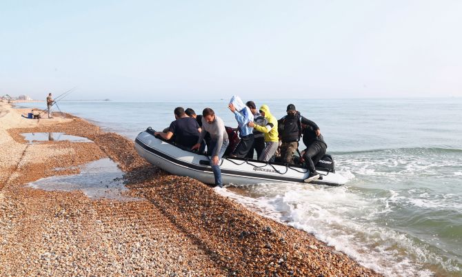 Illegal migrants make a run for it after landing on English beach in rubber dingy