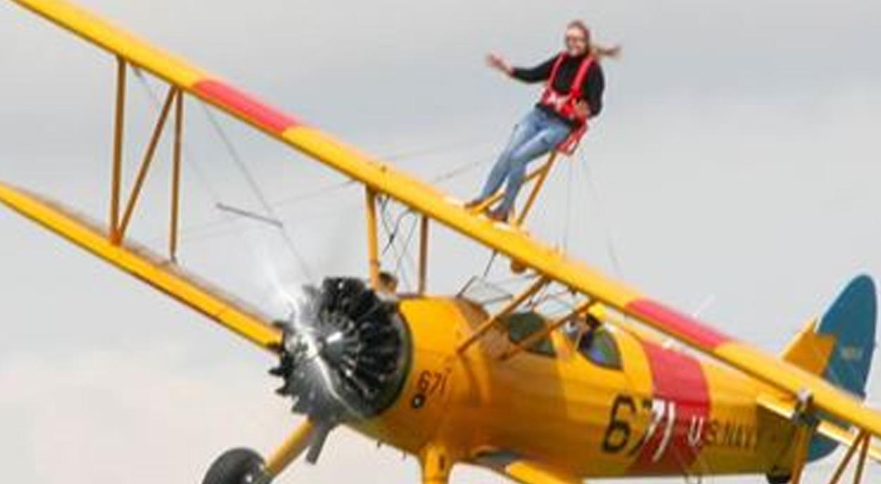 Woman climbs onto wing of plane